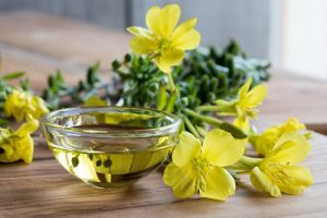 Evening-primrose-oil-in-a-glass-bowl-with-fresh-evening-primrose-flowers-in-the-background_shutterstock_721110889